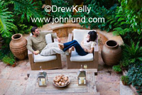 Image of a multi-ethnic couple relaxing outdoors on the patio on a lazy afternoon in a romantic setting at a luxury resort.